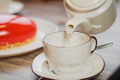 Witte ceramische theepot en kop op de lijst Het water wordt gegoten van de ketel Tegen de achtergrond van roodachtig met suikergl stock fotografie