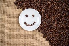 Witte coffeeplate met smiley coffeebeans Royalty-vrije Stock Afbeeldingen