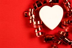Witte decoratieve heartand rode feestelijke wervelingen op een rode achtergrond De ruimte van het exemplaar Feestelijk concept royalty-vrije stock afbeelding