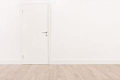 Witte deur en een lichtbruine hardhoutvloer Stock Foto
