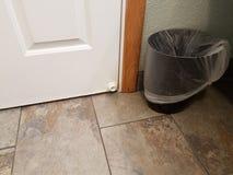 Witte deurkurk met bruine vloertegel en vuilnisbak stock afbeeldingen