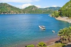 Witte die boot in overzeese die baai wordt verankerd door bergen wordt omringd Royalty-vrije Stock Fotografie