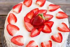 Witte die cake met aardbeien wordt verfraaid op een houten lijst worden geplaatst Stock Foto