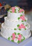 Witte die Huwelijkscake met bloemen van room wordt verfraaid Royalty-vrije Stock Afbeeldingen