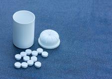 Witte die Pillen over een Blauwe Achtergrond en een Open Fles worden verspreid Hoogste meningsclose-up Royalty-vrije Stock Foto