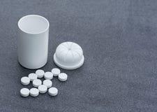 Witte die Pillen over Gray Background en een Open Fles worden verspreid Hoogste meningsclose-up stock foto