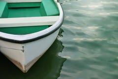 Witte die roeiboot dichtbij kust wordt vastgelegd stock afbeelding
