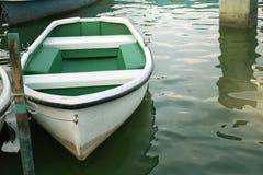 Witte die roeiboot dichtbij kust wordt vastgelegd - Stille het concept, wacht royalty-vrije stock foto's
