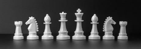 Witte die schaakcijfers op de zwarte achtergrond worden geïsoleerd royalty-vrije stock afbeeldingen