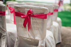 Witte die stoelen met roze linten voor huwelijksceremonie worden verfraaid Royalty-vrije Stock Afbeeldingen