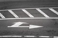 Witte die verkeersteken in asfalt worden geschilderd Stock Afbeelding