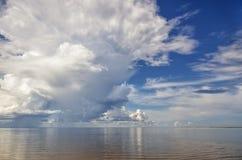 Witte donderwolken over het overzees tegen de blauwe hemel royalty-vrije stock foto