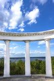Witte Dorische kolommen blauwe hemel met wolken Stock Foto