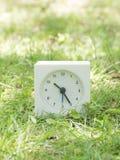Witte eenvoudige klok op gazonwerf, 10:25 tien vijfentwintig Stock Afbeeldingen