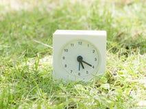 Witte eenvoudige klok op gazonwerf, 5:20 vijf twintig Stock Afbeeldingen