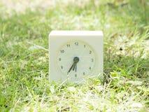 Witte eenvoudige klok op gazonwerf, 6:35 zes vijfendertig Stock Foto