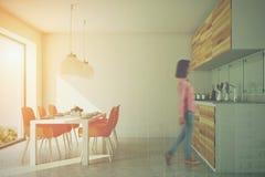Witte eetkamer en keuken, oranje gestemde stoelen Stock Foto