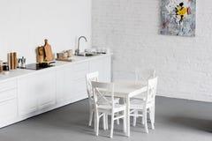witte eettafel bij moderne keuken met wit stock afbeelding