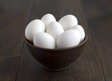 Witte eieren in kom op de houten lijst Stock Foto