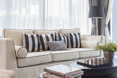 Witte elegantiebank met zwart-witte hoofdkussens in luxelivin Stock Afbeelding