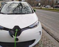 Witte Elektrische auto die op de straat laden stock fotografie