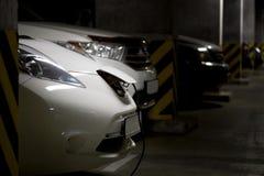 Witte elektrische auto in ondergronds parkeren De auto van de brandstofbenzine op achtergrond Verbonden machtsstop Toekomstige au royalty-vrije stock afbeelding