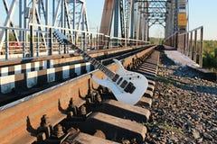 Witte elektrische gitaar op de spoorwegsporen en de stenen Stock Foto