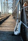 Witte elektrische gitaar op de spoorwegsporen en de stenen Stock Fotografie