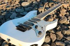 Witte elektrische gitaar op de spoorwegsporen en de stenen Royalty-vrije Stock Fotografie