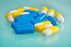 Witte en blauwe pillen op een medische lijst Stock Afbeelding