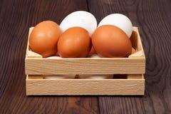 Witte en bruine eieren in houten krat op houten achtergrond stock fotografie