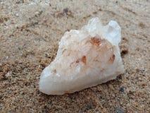 Witte en bruine kristalsteen met textuur op het zand geweven behang als achtergrond, strand Oceaan stock afbeeldingen