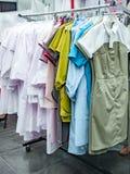 Witte en gekleurde medische robes op hangers royalty-vrije stock afbeelding