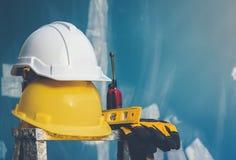 Witte en gele helm met waterspiegel, handschoenen en radio die op de vouwende ladder worden geplaatst stock fotografie