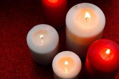 Witte en rode brandende kaarsen op rode achtergrond Stock Foto