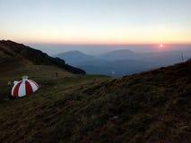 Witte en rode schuilplaats op een bergrand tijdens zonsopgang Stock Afbeeldingen