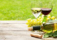 Witte en rode wijnglazen, wijnfles en witte druif Stock Foto's