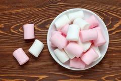 Witte en roze heemst op een schotel op de donkere houten lijst Royalty-vrije Stock Foto's