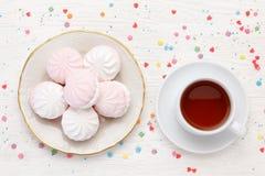 Witte en roze heemstzefier en kop thee op een houten lijst stock fotografie