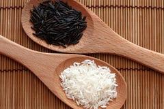 Witte en wilde rijst in houten lepels Stock Afbeeldingen