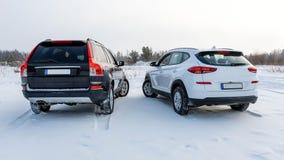 Witte en zwarte die suvauto op een sneeuwgebied wordt geparkeerd Achter mening royalty-vrije stock fotografie