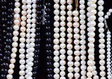 Witte en zwarte parels op een zwarte achtergrond stock afbeelding