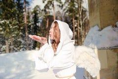 Witte engel die sneeuw van handen wegblaast Stock Foto