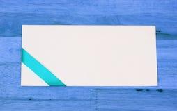 Witte envelop met een groen lint op blauwe houten lijst Royalty-vrije Stock Afbeeldingen