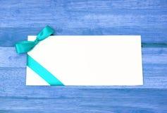 Witte envelop met een groen lint op blauwe houten lijst Stock Fotografie