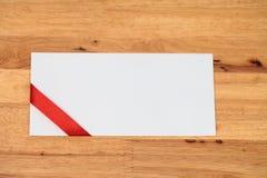 Witte envelop met een groen lint op blauwe houten lijst Royalty-vrije Stock Afbeelding