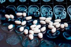 Witte farmaceutische geneeskundepillen op de magnetische achtergrond van het aftastenmri van de hersenenresonantie Apotheekthema, royalty-vrije stock afbeelding