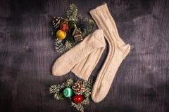 Witte gebreide sokken en Kerstmisdecoratie op een grijze houten achtergrond stock afbeelding