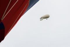 Witte gekleurde blimp, hete luchtluchtschip in grijze hemel in regenachtige dag dichtbij met levendige roodgloeiende Luchtballon  stock foto's