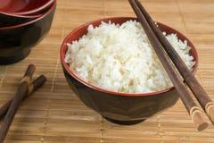 Witte gestoomde rijst in een kom met eetstokjes stock foto's